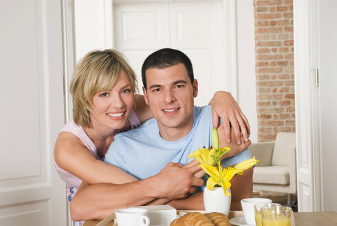 Young couple hugging at breakfast table, close-up - NH00618
