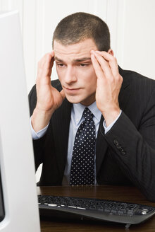 Businessman with hands on forehead looking at pc-screen, close-up, portrait - NH00591