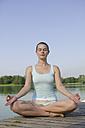 Woman (20-25) exercising yoga on jetty - CKF00151