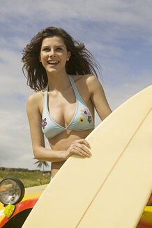 Guadeloupe, Caribbean, Young woman with surfboard - AB00163