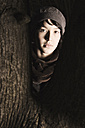 Young woman standing between tree trunk - DW00131