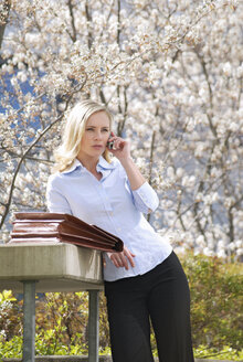 Businesswoman using mobile phone, outdoors - VRF00057