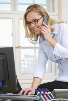 Woman in office using phone, close-up - VRF00038