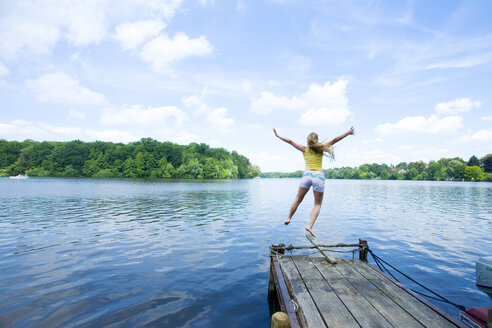 Woman Jumping into Lake, rear view - SEF00015
