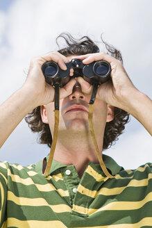 Man using binoculars, close-up - LDF00520