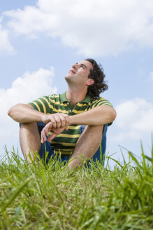 Man sitting in meadow, close-up - LDF00517