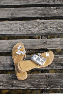 Italy, Lake Garda, Sandals and handy on wooden dock, close-up - DKF00124