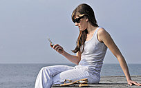 Italy, Lake Garda, Womann 20-25)  sitting on edge of dock with mobile phone, side view - DKF00121