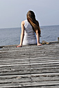 Italy, Lake Garda, Young woman (20-25) sitting on dock, rear view, close-up - DKF00118