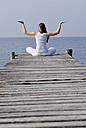 Italy, Lake Garda, Woman (20-25) exercising yoga on jetty - DKF00112