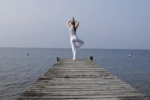 Italy, Lake Garda, Woman (20-25) exercising yoga on jetty - DKF00109
