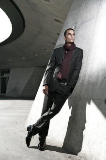 Man leaning on wall, wearing suit - OW00839
