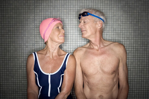 Senior couple in changing room, wearing swim cap and goggles - BABF00487
