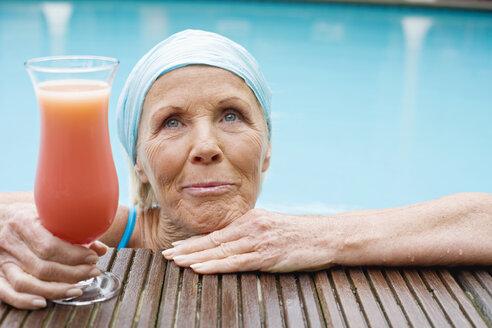 Germany, senior woman having cocktail at pool - BABF00286