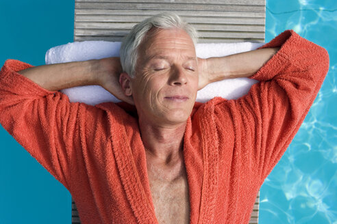 Germany, senior man relaxing on float in pool, close-up, portrait - BABF00244