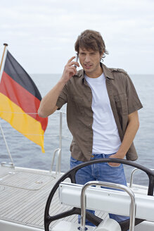 Germany, Baltic Sea, Lübecker Bucht, Young man on yacht using mobile phone - BAB00453