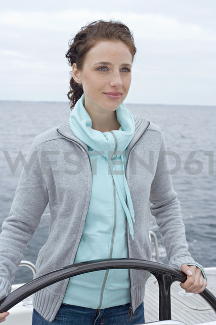 Young woman at ship's wheel, portrait - BAB00435