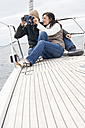 Germany, Baltic Sea, Lübecker Bucht, Young couple on boat, man looking through binoculars - BAB00396
