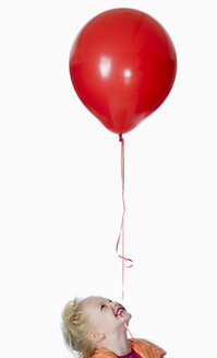 Girl (8-9) with red balloon in mouth, portrait - KMF01139