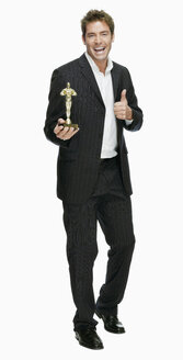 Young man with film award, thumbs up, portrait - KMF01106
