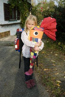 Girl (6-7) holding school cone, smiling, portrait, - NHF00674