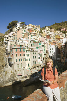 Italy, Liguria, Riomaggiore, Woman sitting on stone wall - MRF01025