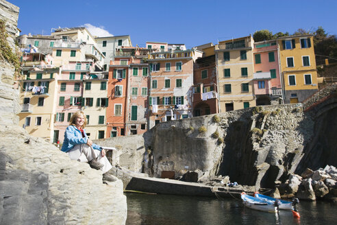 Italy, Liguria, Riomaggiore, Woman sitting on rock - MRF00956