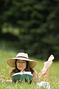 Young woman holding book, lying in meadow - HHF01758