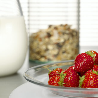 Strawberries on plate, cereals and milk in background - CHKF00465