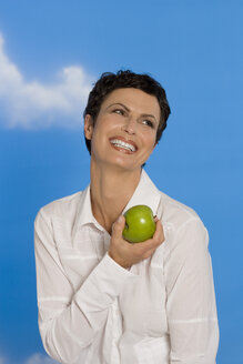 Young woman holding apple, smiling, portrait - RRF00097