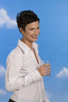 Young woman holding glass of water, smiling, portrait - RRF00088