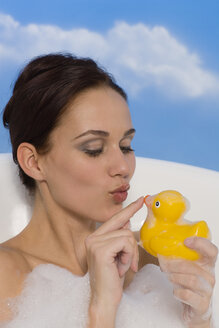 Young woman in bath holding rubber Duck, portrait - RRF00019