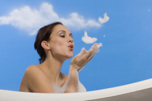 Young woman in bubble bath, blowing suds from hands, side view - RRF00016