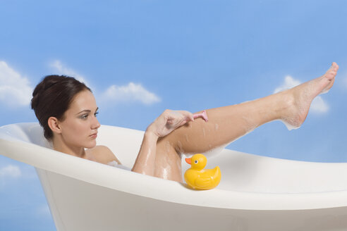 Young woman shaving legs in bath - RRF00001