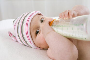 Baby boy  (6-9 months) drinking milk from bottle, portrait - SMOF00098