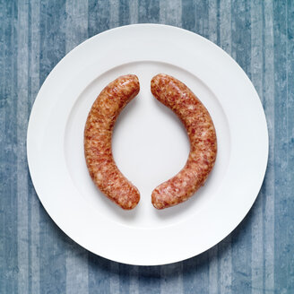 Raw sausages on plate, elevated view - MU00120