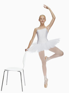 Young ballerina (14-15) standing on pointe in toe shoes,, portrait - KMF01167