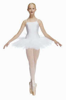 Young ballerina (14-15) standing on pointe in toe shoes,, portrait - KMF01155