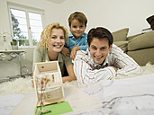 Young family in living room, smiling, portrait - WESTF06661