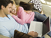 Young couple on sofa, man using laptop, smiling, portrait - WESTF06561