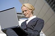 Business woman using laptop, portrait - MAEF00814