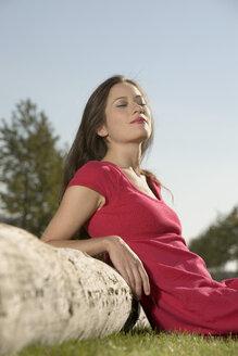 Woman leaning on tree trunk, portrait - LDF00560