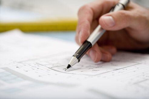 Man's hand pointing at blueprint with pen - HKF00073