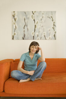 Young woman sitting on sofa, portrait - WESTF07381