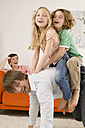Boy (6-7) and girl (8-9) on father's back in living room - WESTF07343