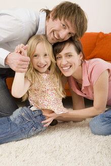 Playful family in living room, portrait - WESTF07334