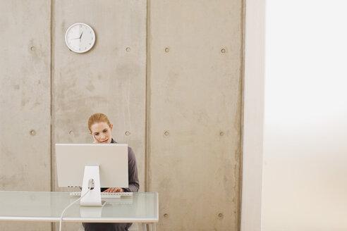 Businesswoman using a laptop, portrait - WESTF07952
