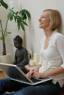 Blonde woman using laptop, portrait - DKF00162