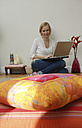 Blonde woman using laptop, portrait - DKF00159