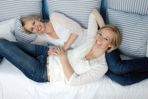 Two blonde women relaxing on bed, portrait - DKF00144